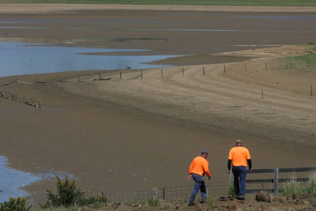 RAIN, HAIL AND DROUGHT: Workers inspect a reservoir during the Millennial Drought, one of many extreme weather events a Harcourt farmer has been through in the last 20 years. Picture: ANGELA WYLIE