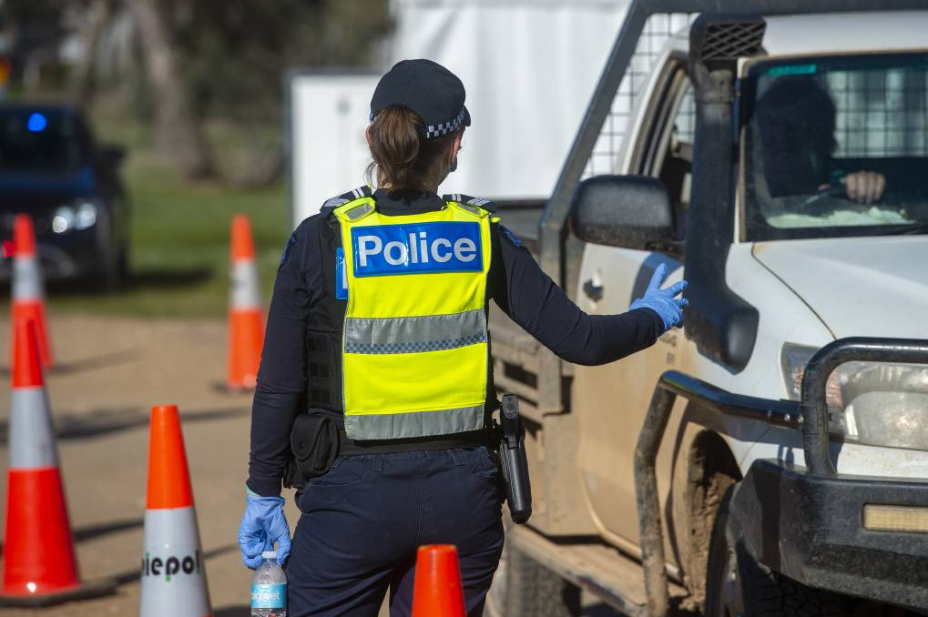 A police officer at a COVID-19 checkpoint. Picture: DARREN HOWE