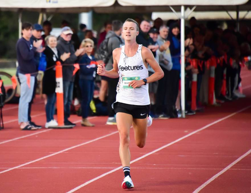 Andy Buchanan receives support from the crowd as powers to the finish line to win the 5km Frenzy. Picture: BRENDAN McCARTHY