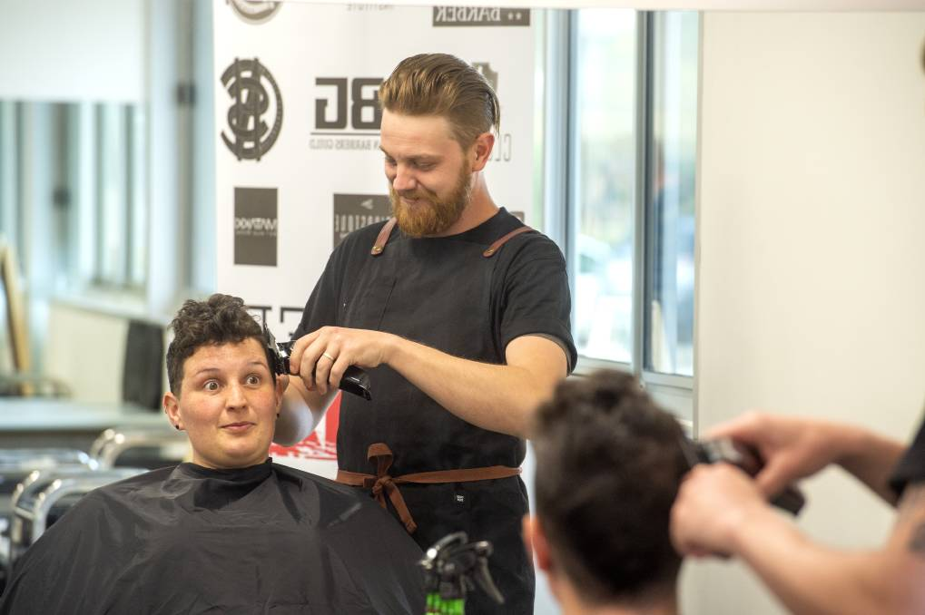AT WORK: Samuel Pearce cuts Rebecca Labouchardiere's hair. Picture: DARREN HOWE